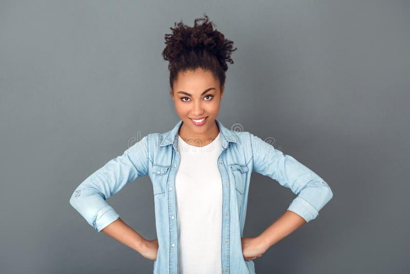 Jeune femme africaine d'isolement sur les mains quotidiennes occasionnelles de mode de vie de studio gris de mur sur la taille image stock
