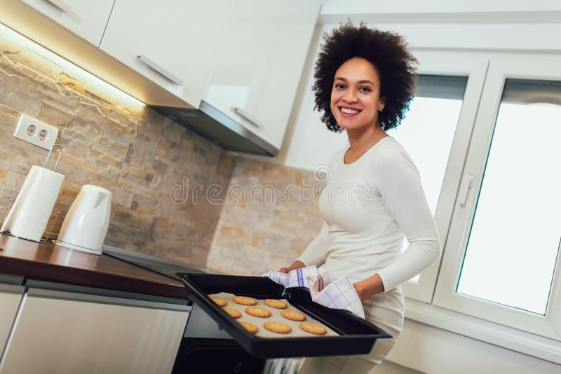 Jeune femme africaine enlevant le four de Tray Of Baked Cookies From photos stock