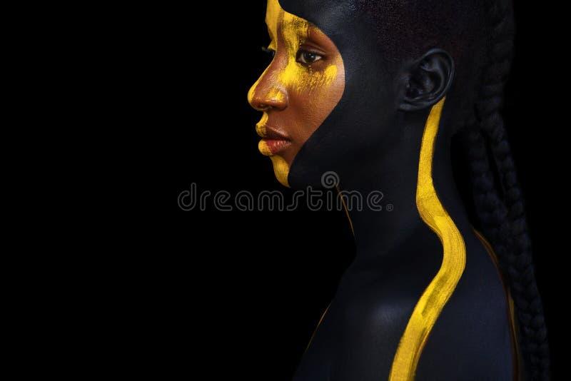 Jeune femme africaine gaie avec le maquillage de mode d'art Une femme étonnante avec le maquillage noir et jaune de peinture images libres de droits