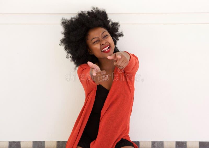 Jeune femme africaine gaie dirigeant des doigts et cligner de l'oeil image stock