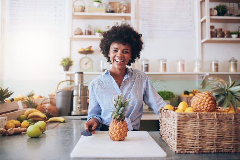 Jeune femme africaine gaie travaillant au bar à jus photos stock