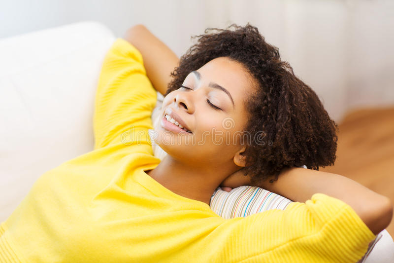 Jeune femme africaine heureuse détendant à la maison photos stock