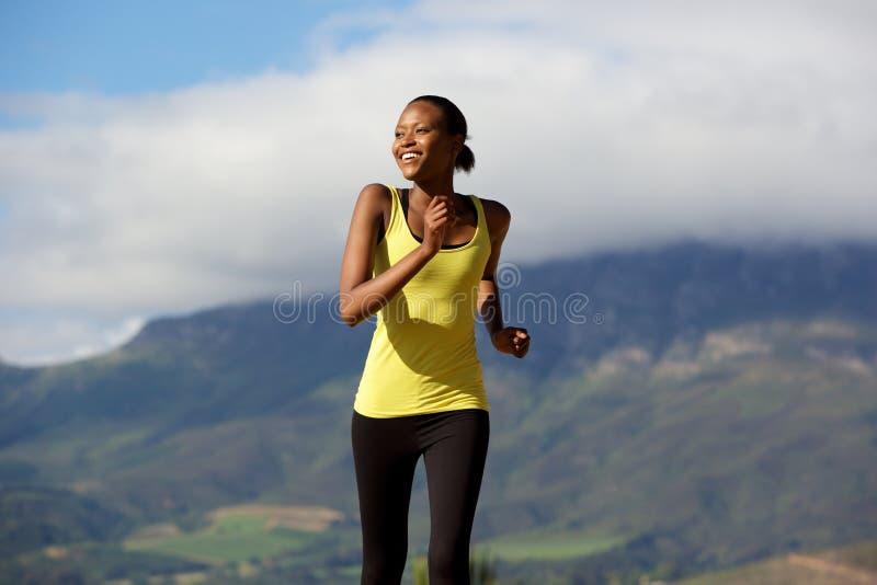 Jeune femme africaine heureuse faisant la séance d'entraînement courante photographie stock libre de droits