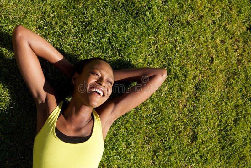 Jeune femme africaine heureuse se reposant sur l'herbe après séance d'entraînement images stock