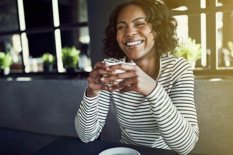 Jeune femme africaine riante buvant du café frais dans un café image libre de droits