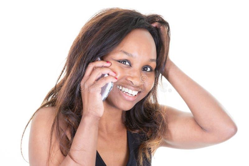 Jeune femme africaine sur des mains de téléphone portable sur des poils image stock