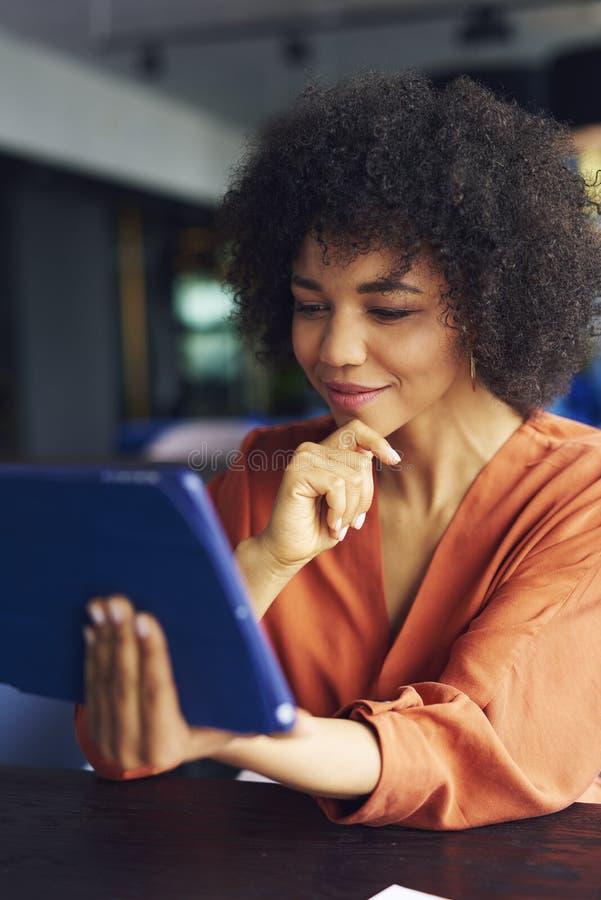Jeune femme africaine travaillant avec la technologie photos stock