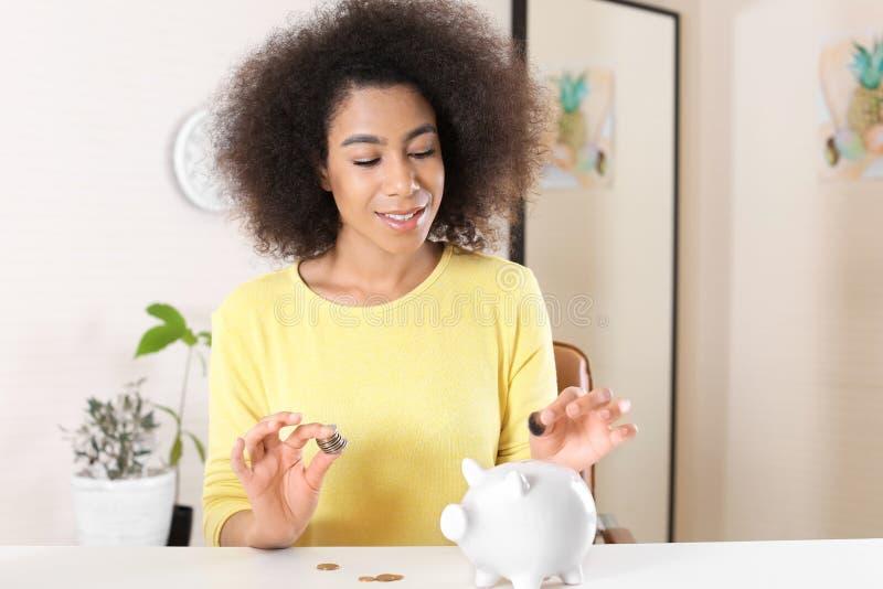 Jeune femme afro-américaine mettant l'argent dans la tirelire à la maison Concept de l'?pargne images stock