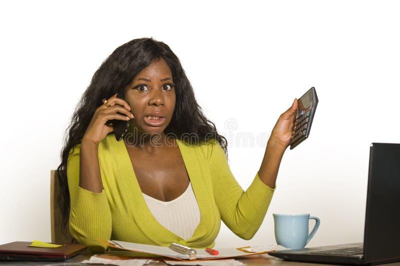 Jeune femme afro-américaine noire attirante et occupée d'affaires travaillant à la maison le bureau d'ordinateur de bureau parlan images stock