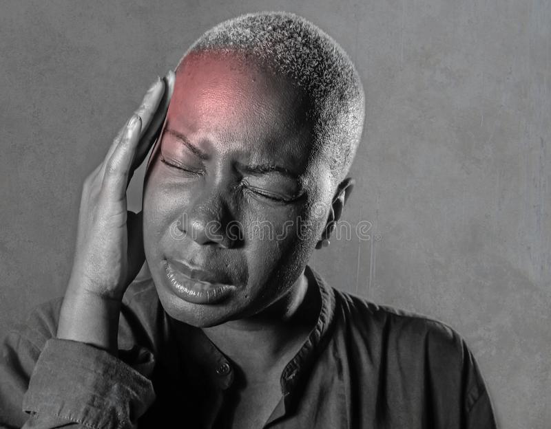 Jeune femme afro-américaine noire attirante et triste avec des doigts sur son sentiment de souffrance de mal de tête et de migrai photographie stock