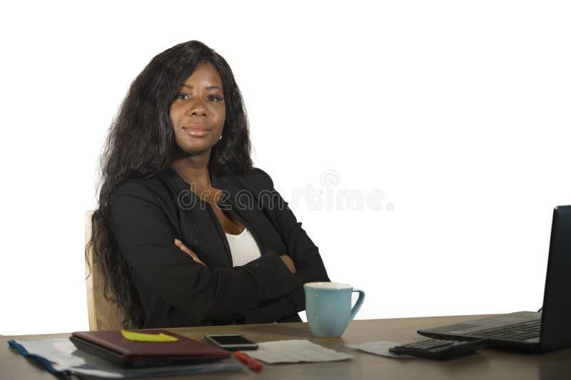 Jeune femme afro-américaine noire heureuse et attirante d'affaires travaillant à la pose réussie de sourire de bureau d'ordinateu photos libres de droits