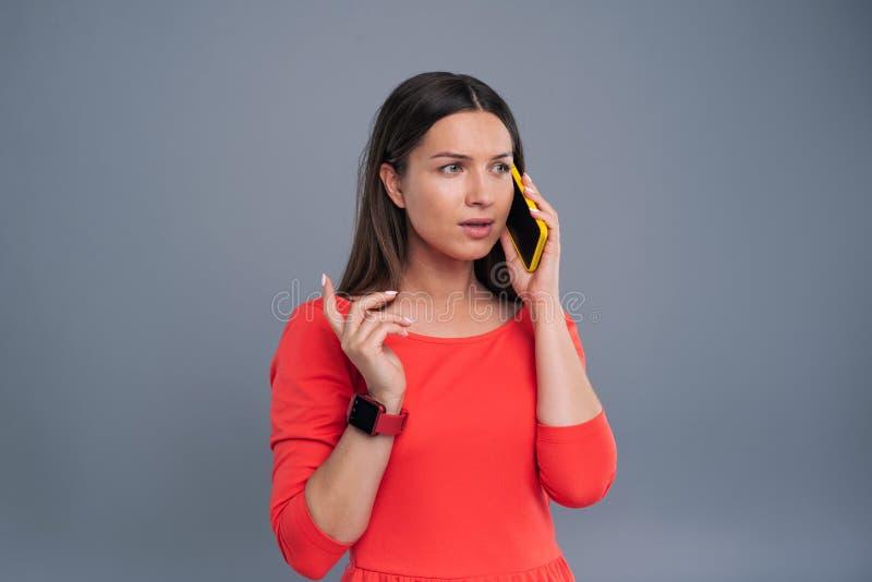 Jeune femme agréable dans la robe rouge ayant l'appel téléphonique images stock