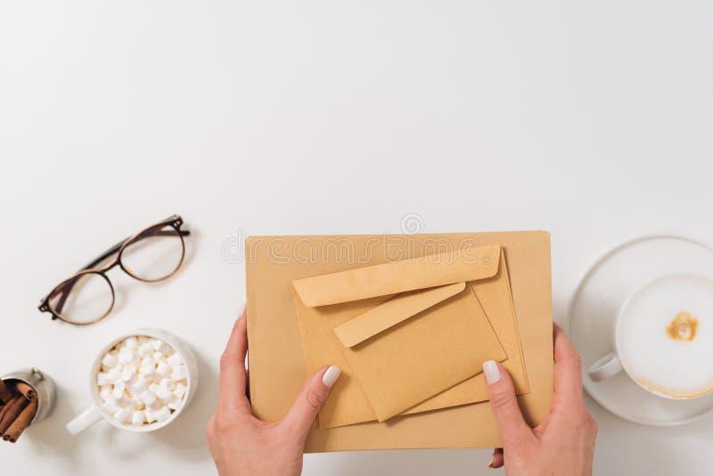 Jeune femme agréable tenant les enveloppes de papier image stock