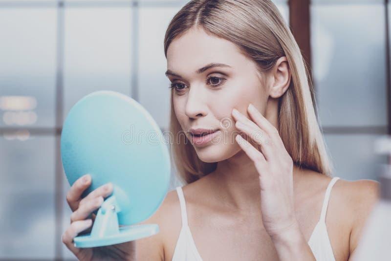 Jeune femme agréable tenant un miroir photo stock