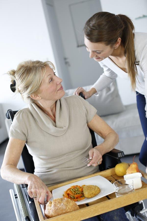 Jeune femme aidant la femme supérieure dans le fauteuil roulant photo stock