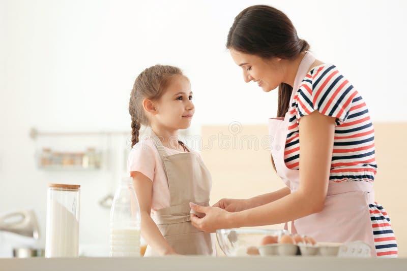 Jeune femme aidant sa fille à mettre dessus le tablier dans la cuisine Faisant la pâte ensemble photographie stock