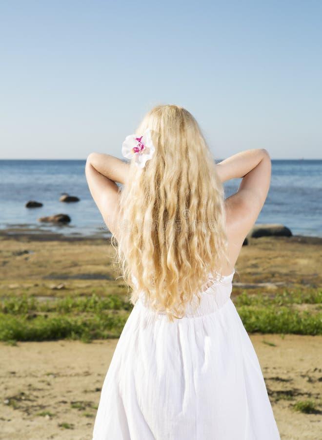 Jeune femme ajustant ses poils d'or images stock