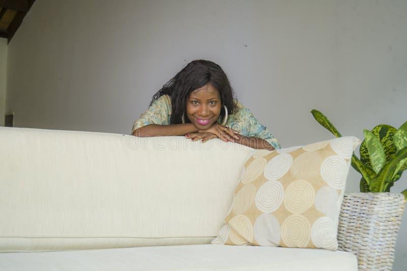 Jeune femme américaine élégante de beau et heureux africain noir posant au divan de sofa de salon dans son sourire moderne d'appa photo libre de droits