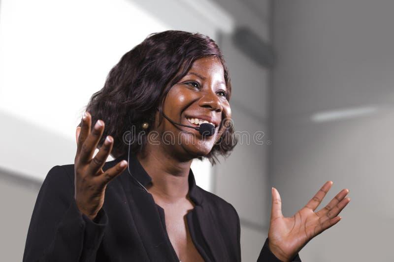 Jeune femme américaine d'affaires d'africain noir attirant et sûr avec le casque parlant dans l'amphithéâtre à la formation d'ent image libre de droits
