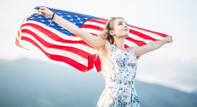 Jeune femme américaine heureuse tenant le drapeau des Etats-Unis images stock