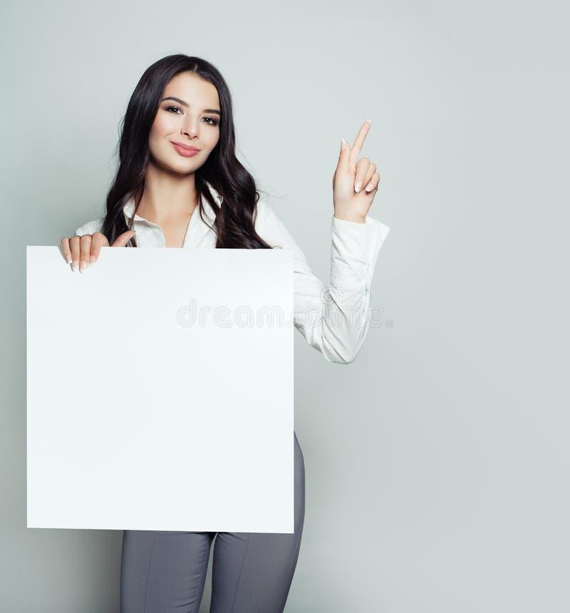 Jeune femme amicale avec la bannière blanche vide de papier blanc image stock