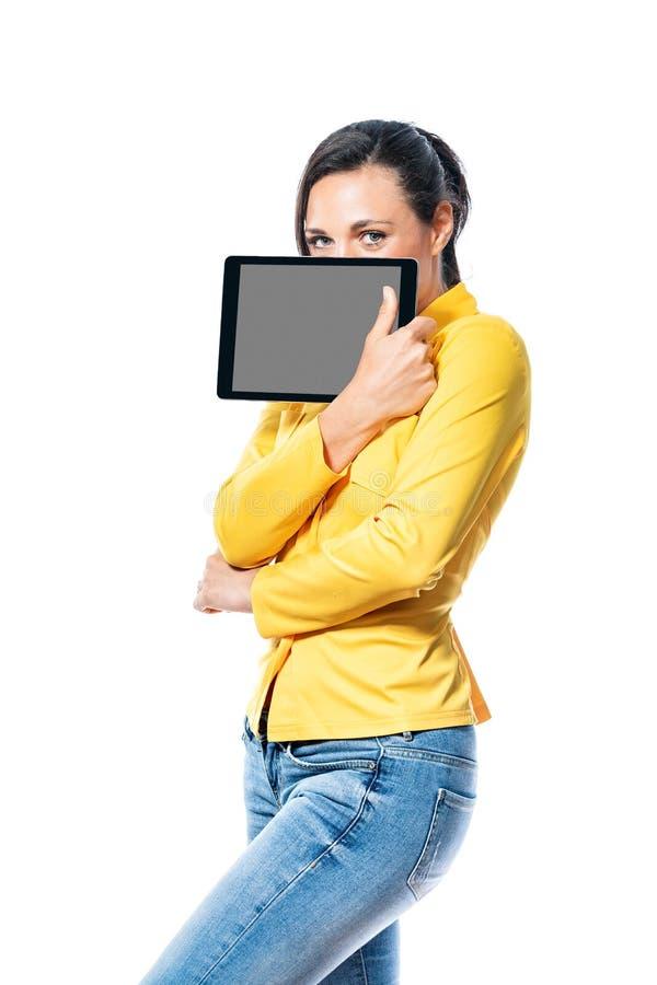 Jeune femme amicale de sourire tenant un comprimé photo stock