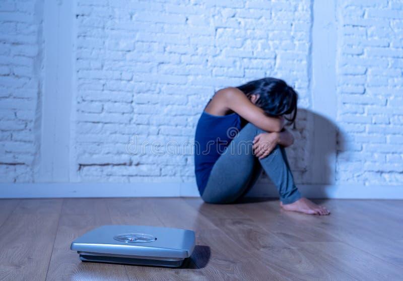 Jeune femme anorexique d'adolescent seul s'asseyant sur la terre regardant l'échelle inquiétée et déprimée en suivant un régime e images stock