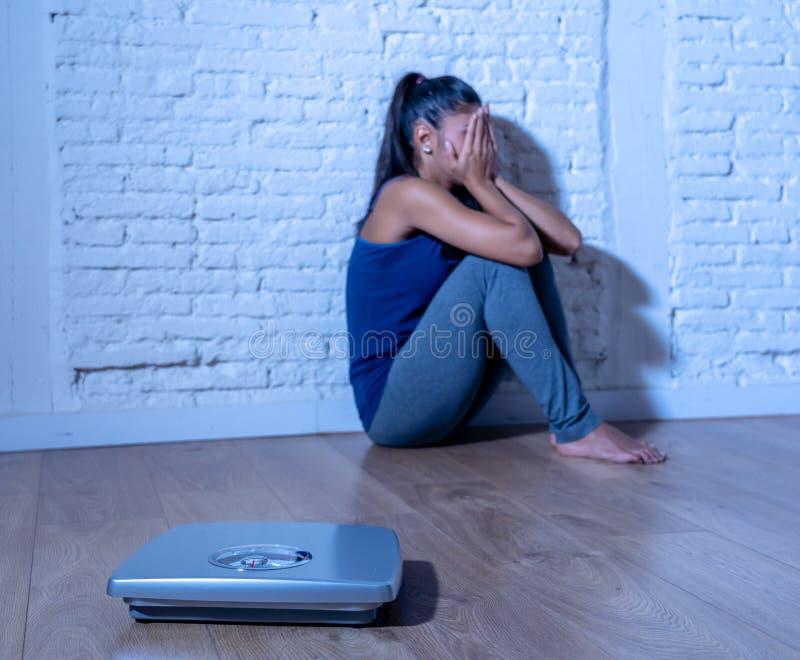 Jeune femme anorexique d'adolescent seul s'asseyant sur la terre regardant l'échelle inquiétée et déprimée en suivant un régime e image libre de droits