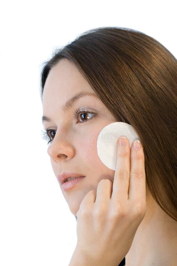 Jeune femme appliquant des garnitures de coton de visage photos stock