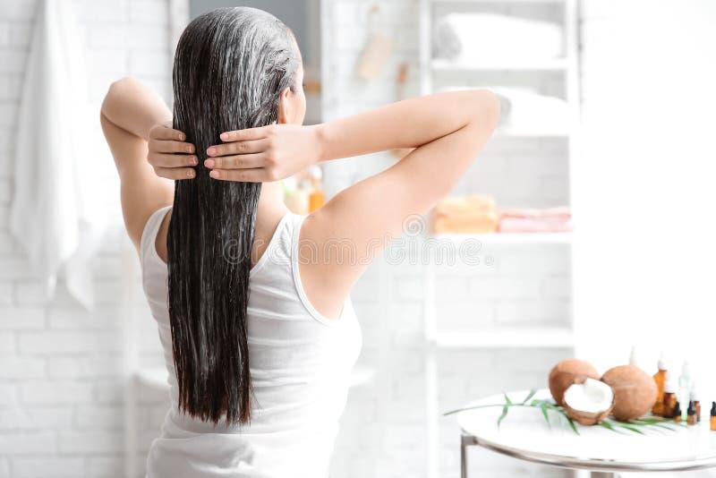 Jeune femme appliquant l'huile sur des cheveux photos libres de droits