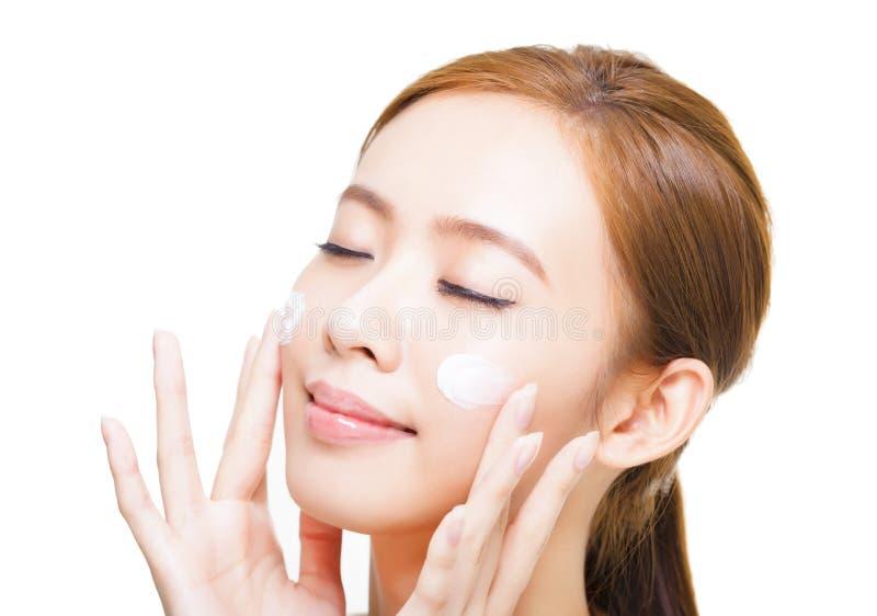 Jeune femme appliquant la crème cosmétique sur son visage photos stock