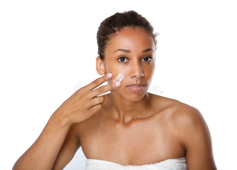 Jeune femme appliquant la crème de beauté sur le visage photographie stock libre de droits