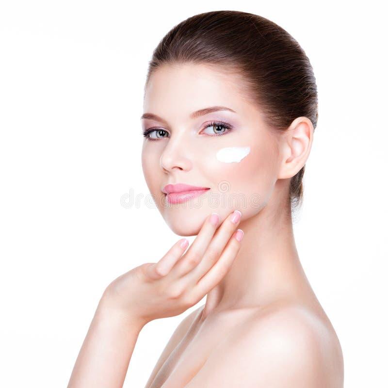 Jeune femme appliquant la crème sur son joli visage photographie stock libre de droits