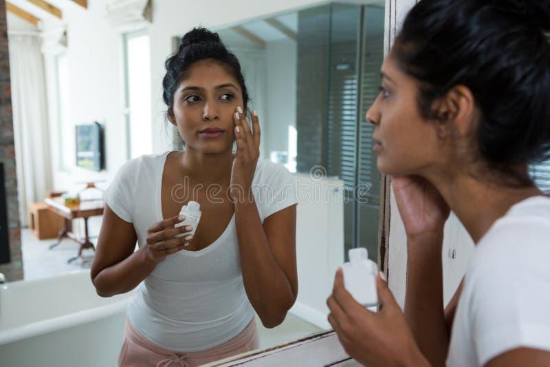 Jeune femme appliquant la lotion images stock