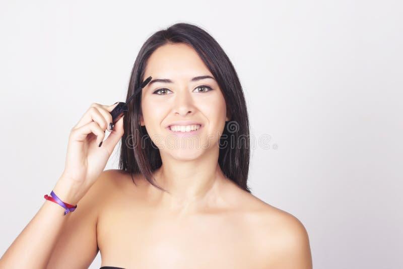 Jeune femme appliquant le mascara sur ses cils images libres de droits