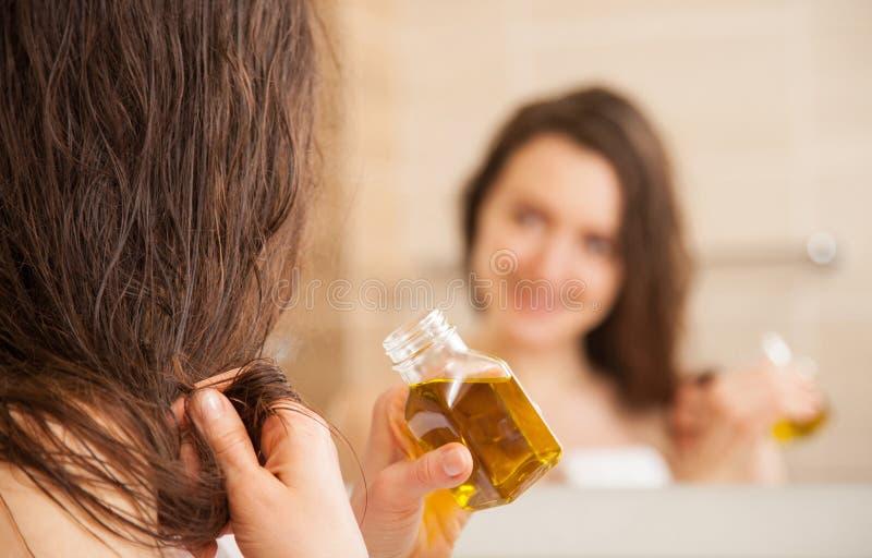 Jeune femme appliquant le masque d'huile aux astuces de cheveux photographie stock libre de droits