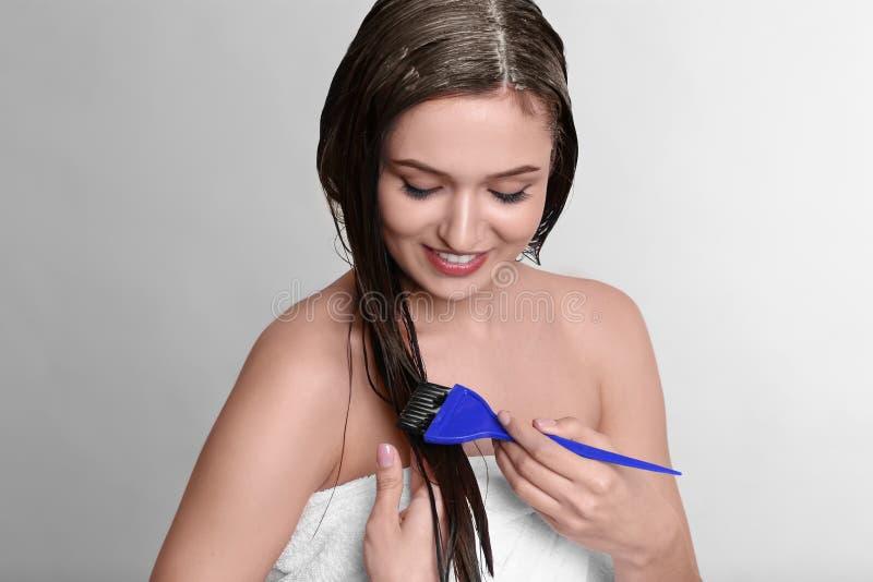 Jeune femme appliquant le masque sur ses cheveux images stock