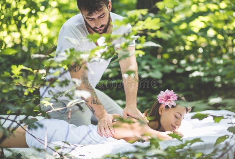 Jeune femme appréciant détendant le massage de corps à la nature photographie stock