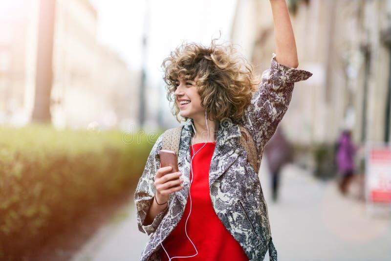 Jeune femme appréciant la musique dehors photographie stock