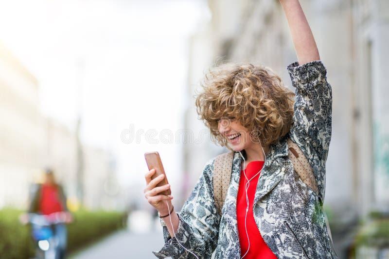 Jeune femme appréciant la musique dehors photos stock