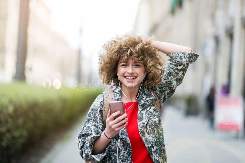 Jeune femme appréciant la musique dehors images stock