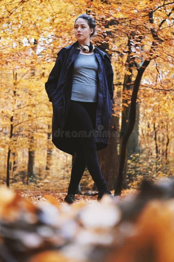 Jeune femme appréciant la promenade d'automne dans les bois photo libre de droits