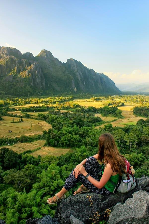 Jeune femme appréciant la vue des champs de ferme dans Vang Vieng, Laos photographie stock