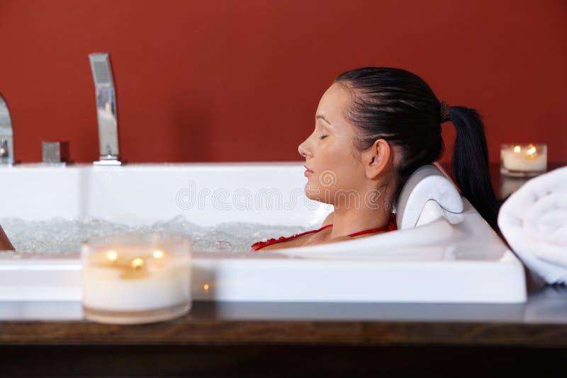 Jeune femme appréciant le bain de bulle photographie stock libre de droits