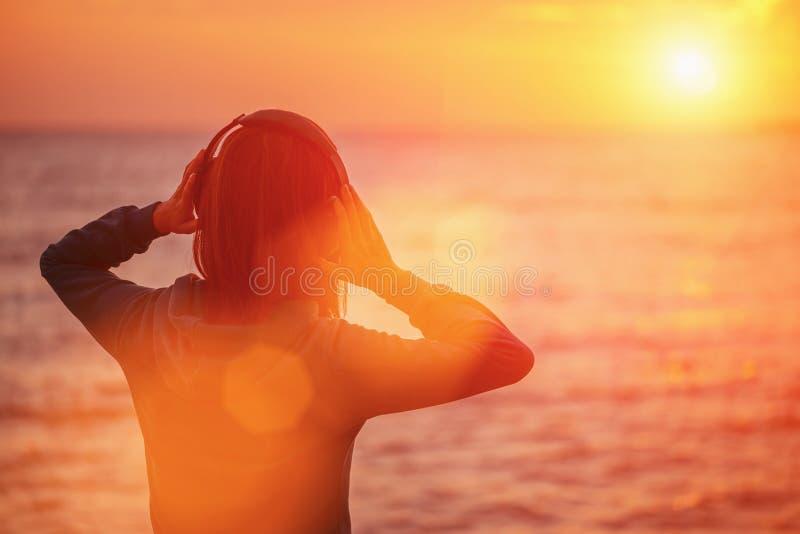 Jeune femme appréciant le beau coucher du soleil au-dessus de la mer photo stock