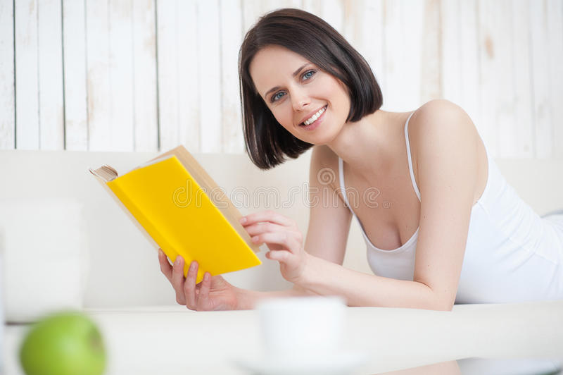 Jeune femme appréciant le bon livre photo libre de droits