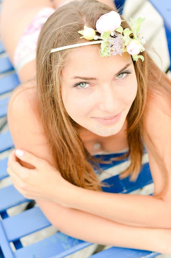 Jeune femme appréciant le jour ensoleillé sur le salon de soleil photos libres de droits