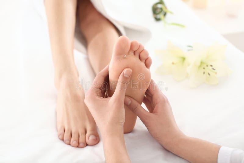 Jeune femme appréciant le massage de pied dans le salon de station thermale, foyer sur des jambes photographie stock