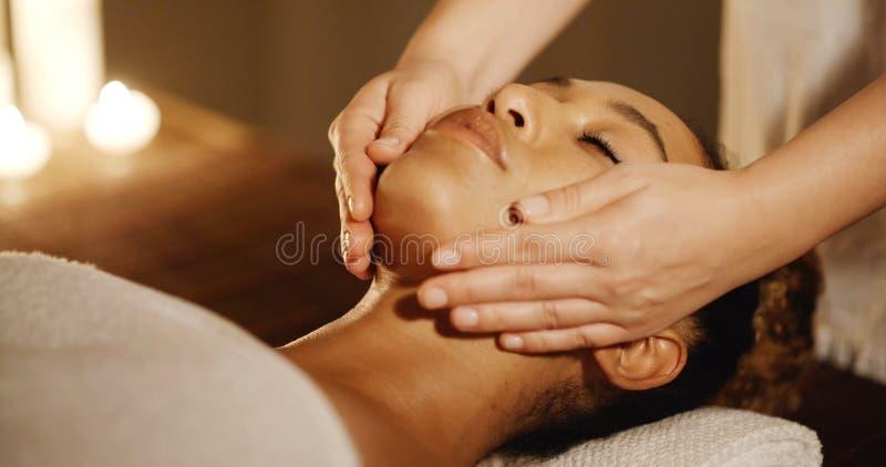 Jeune femme appréciant le massage facial au salon de station thermale photographie stock libre de droits