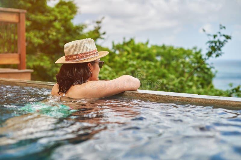 Jeune femme appréciant le temps dans la piscine image stock